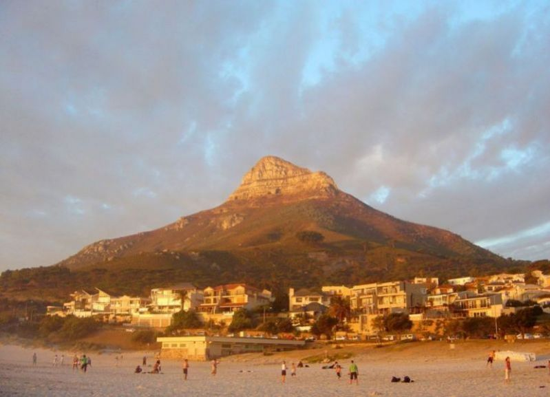 Camps Bay beach at sunset with Lions head in background in background